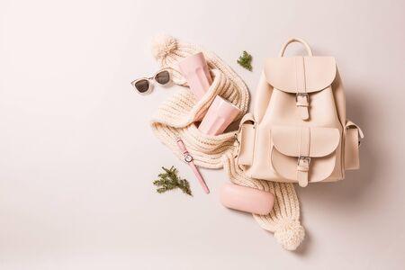 Accessoires de mode d'hiver ou d'automne - cadeaux de Noël. Sac à dos en cuir blanc, écharpe en laine, mugs rose pastel, montre et lunettes de soleil. Capturé d'en haut (vue de dessus, mise à plat) sur fond gris.
