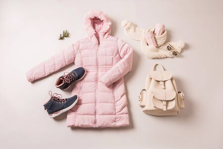 Winter outfit for women - pastel pink down (duvet) jacket, boots, white leather backpack and woollen scarf. Captured from above (top view, flat lay) on grey background.