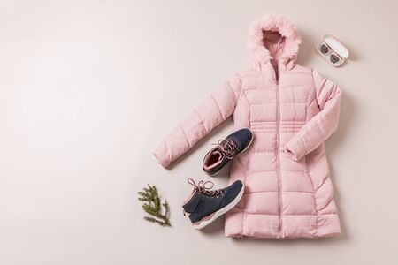 Winter outfit for women - pastel pink down (duvet) jacket and dark blue boots. Captured from above (top view, flat lay) on grey background. Layout with free copy (text) space. 版權商用圖片