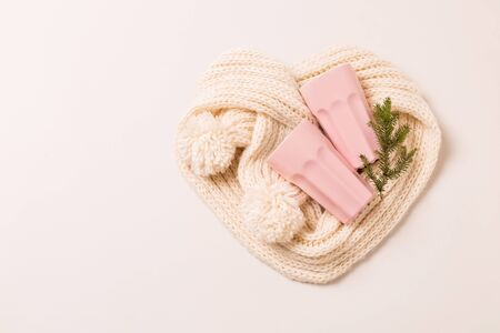Pastel pink mugs and white woollen scarf arranged into a heart shape. Winter - christmas gifts concept. Background layout with free copy (text) space. Stockfoto