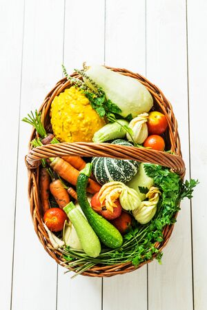 Colorful organic vegetables in wicker basket. Captured from above (top view) on white wooden background. Layout with free text (copy) space. Fresh harvest from the garden. 版權商用圖片