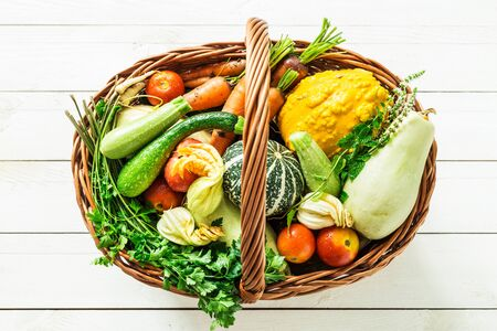 Colorful organic vegetables in wicker basket. Captured from above (top view) on white wooden background. Fresh harvest from the garden.
