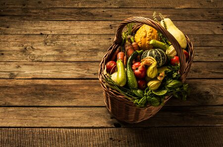 Colorful organic vegetables in wicker basket - captured from above (top view) on wooden background. Layout with free text (copy) space. Fresh harvest from the garden. 版權商用圖片