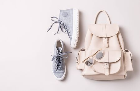 Fashion - shoes and accessories. White leather backpack, pastel blue sneakers and sunglasses. Cool young look design - captured from above (top view, flat lay). Layout with free copy space.