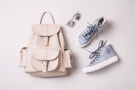Fashion - shoes and accessories. White leather backpack, pastel blue sneakers and sunglasses. Cool young look design - captured from above (top view, flat lay).