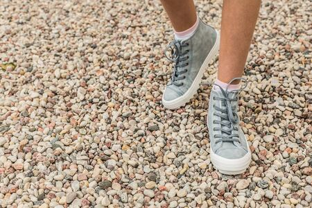 Pastel blue sneakers on legs outdoor - closeup. Stone beach as background. Footwear - layout with free copy (text) space.