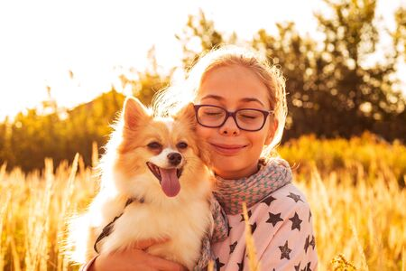 Young smiling child girl holding a pomeranian (spitz) dog outdoor on the meadow - happy childhood concept. Gold sunset light.