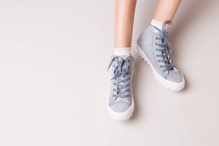Pastel blue sneakers on legs. Footwear on grey background. Layout with free copy (text) space.