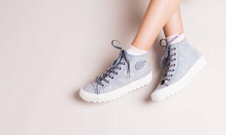 Pastel blue sneakers on crossed legs. Footwear on grey background. Layout with free copy (text) space. 版權商用圖片