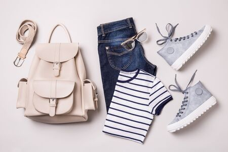 Clothing and accessories - white backpack, jeans, striped t shirt, blue sneakers, sunglasses and belt. Classic casual fashion outfit captured from above (top view, flat lay). Cool young look design.