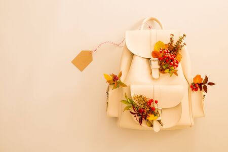 Mochila de piel blanca decorada con hojas de otoño y etiqueta en blanco (etiqueta). Concepto estacional - fondo con espacio de copia (texto) gratuito. Capturado desde arriba (vista superior, plano). Foto de archivo