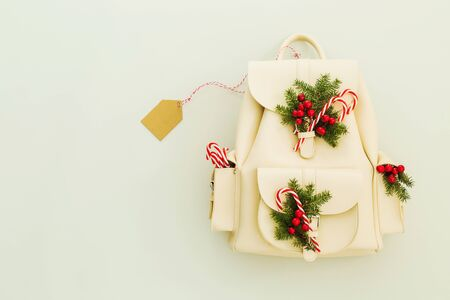 Christmas gift concept. White leather backpack with decorations (candy canes and pine branches). Blank tag (label) on the background. Captured from above (top view, flat lay), free copy (text) space.
