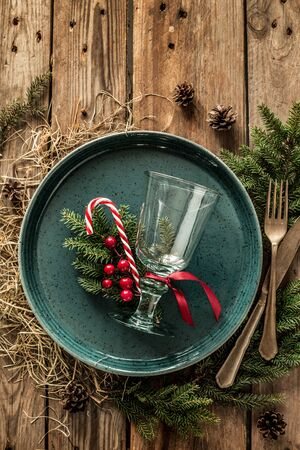 Rustic christmas table setting design captured from above (top view, flat lay). Turquoise plate, glass, cutlery, candy cane and natural decorations. Wooden background with free copy (text) space.