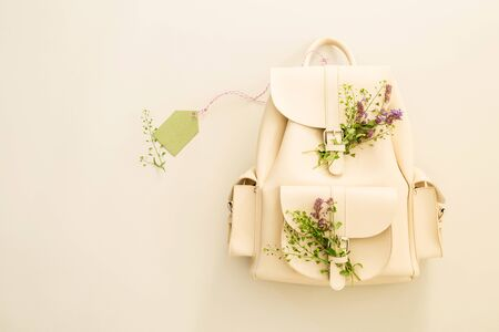White leather backpack decorated with spring meadow flowers and blank pastel green tag (label). Seasonal concept - background with free copy (text) space. Captured from above (top view, flat lay).