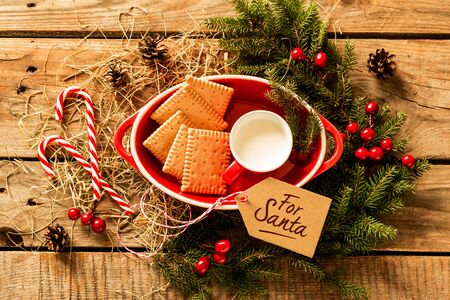 Cookies and milk prepared for Santa Claus on wooden table with decorations around. Celebrating christmas traditions. Composition captured from above (top view, flat lay). 版權商用圖片