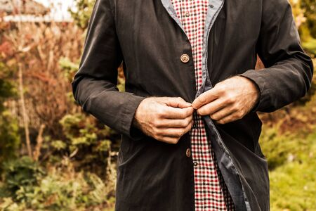 Clothing - casual fashion. Man in plaid shirt buttons dark blue jacket. Outdoor - autumn garden as background.