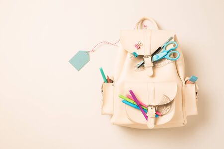 White leather backpack decorated with school supplies and blank pastel blue tag (label). Background with free copy (text) space. Captured from above (top view, flat lay).