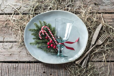Rustic christmas table setting design captured from above (top view, flat lay). Gray plate, glass, cutlery, candy canes and natural decorations on wooden background.