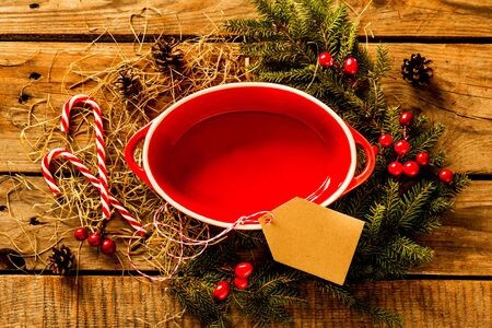 Christmas background with red empty oval ceramic baking dish. Blank tag and rustic natural decorations on wooden table.
