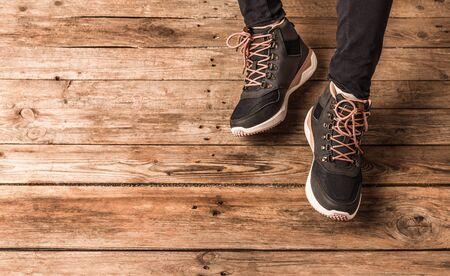 Footwear - dark blue trekking shoes (boots) on legs. Wooden background with free copy (text) space. Foto de archivo - 133743765