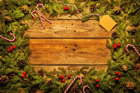 Christmas - natural green pine branches frame (border) with candy canes and decorations. Wooden background with free copy (text) space. Rustic layout captured from above (top view, flat lay).