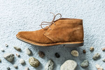 Fashion - men's camel suede desert shoe (boot) on grey concrete background with stones. Footwear captured from above (top view). Layout with free copy (text) space.
