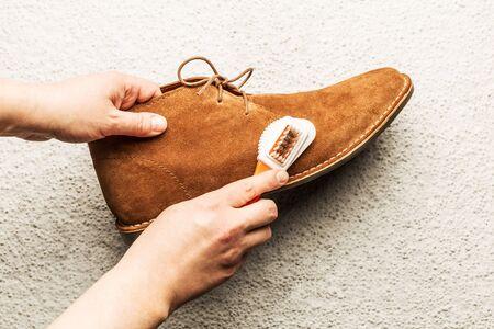 Hände, die den Kamelwildlederwüstenschuh (Stiefel) der Männer mit einer Bürste reinigen. Schuhpflege von oben erfasst (Draufsicht). Grauer Betonhintergrund.