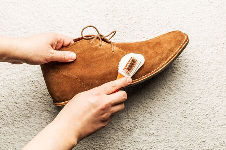 Hands cleaning mens camel suede desert shoe (boot) with a brush. Footwear maintenance captured from above (top view). Grey concrete background. Stock Photo