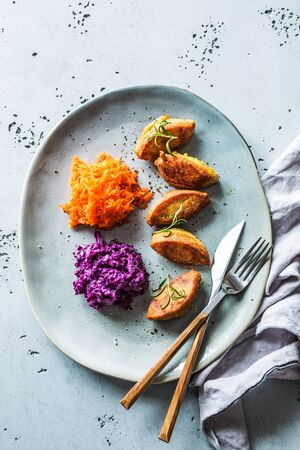 Vegetarian meal - chickpea falafels with carrot and red cabbage salads. Dinner captured from above (top view, flat lay) on a grey plate. Imagens