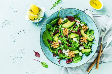Colorful lunch - spring salad. Fresh leaves, avocado, walnuts, feta cheese and olive oil in a blue bowl. Meal captured from above (top view, flat lay) on a pastel stone background. Free copy space.