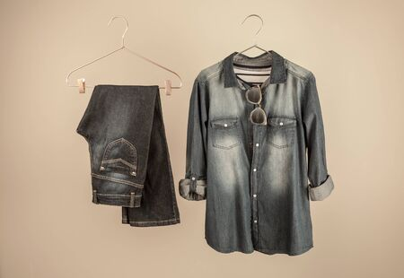 Fashion - denim outfit on hangers. Dark blue womens jeans and a shirt.