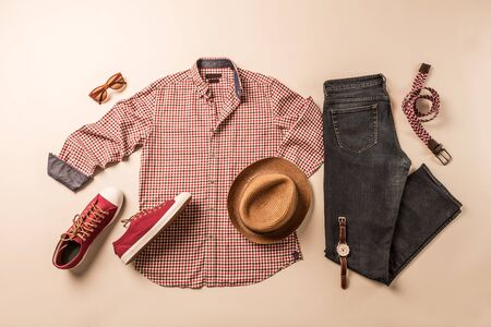 Men's classic casual fashion outfit - clothing and accessories layout. Jeans, plaid shirt and red sneakers captured from above (top view, flat lay). Free copy (text) space. Imagens