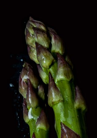 Fresh wet green asparagus close up (macro) on black background captured from above. Dark moody artistic style.