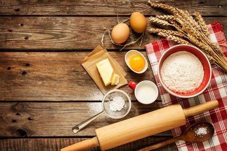 Backen von Kuchen in der ländlichen Küche - Teigrezeptzutaten (Eier, Mehl, Milch, Butter, Zucker) auf Vintage-Holztisch von oben. Hintergrundlayout mit freiem Textraum. Standard-Bild