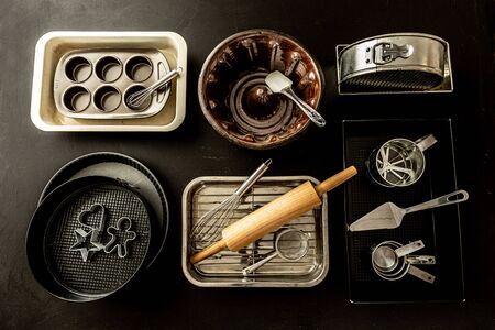 Oven bakeware - baking tins, cake moulds and kitchen utensils. Collection captured from above (top view, flat lay). Black chalkboard background.