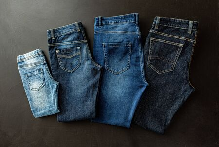 Clothing - family jeans on black chalkboard background. Denim trousers captured from above (top view, flat lay). Various sizes, shapes and blue shades (tones).