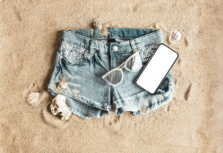 Women's denim shorts, smartphone and sunglasses on the beach. Holiday (vacation) background with free copy (text) space.