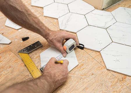 Interior finishing worker (tiler) laying white hexagon ceramic tiles tiles on the floor. Bathroom renovation works. Handyman at work. Standard-Bild