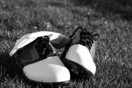 classic black and white photo of golf shoes and glove for the hungry golfer Stok Fotoğraf