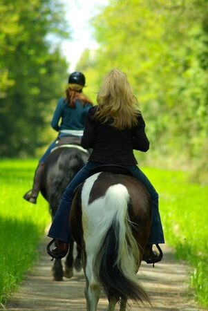 two women take to the trail horse back riding on a sunny afternoon