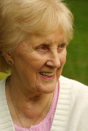 Happy senior looks to the side, possibly chatting with friends