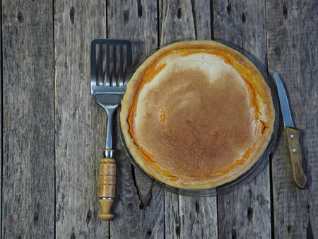 Round homemade pie with pumpkin, chopped walnuts, dipped in beaten eggs with sugar. Wooden rustic background.