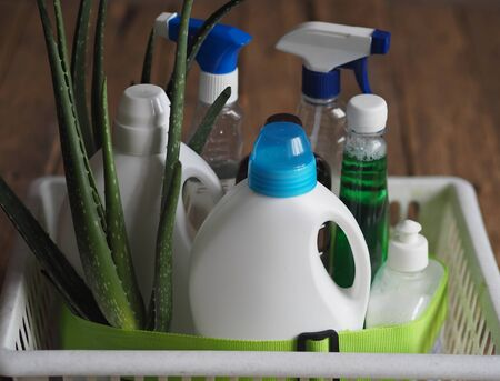 The concept of eco-friendly natural detergents. Detergents and cleaning products with aloe vera plant on a wooden background in a plastic basket for linen.