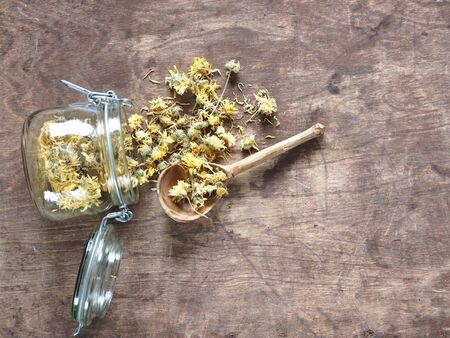 Dried flowers calendula and brewed medicinal tea on a wooden table. Harvesting for the winter.