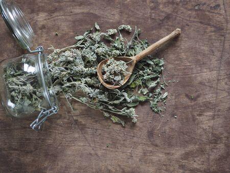 Dry medicinal herb lemon balm, mint. Wood background. Herbal tea for health.