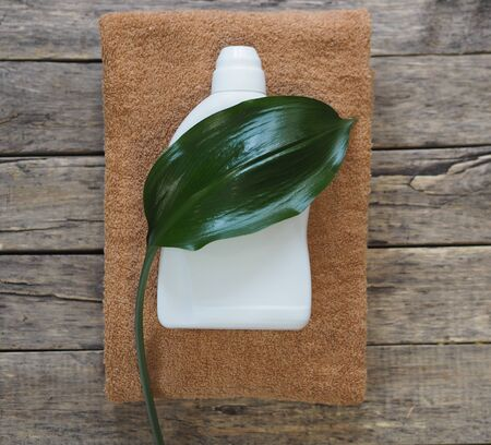 Eco blank design packaging of natural bottles among green grass. Bio organic detergent product. Green leaves of plants. Zdjęcie Seryjne