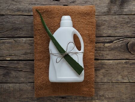 Eco blank design packaging of natural bottles among green grass. Bio organic detergent product. In conjunction with the green leaf of the medicinal plant aloe vera.