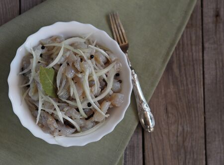 salad of freshly salted pike river fish on a wooden background. With onions and seasoning. Winter fishing. 免版税图像