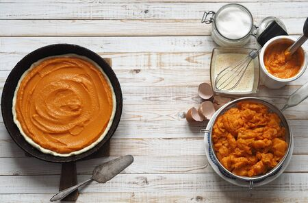 Round homemade pie with pumpkin. Stage of cooking. We spread the filling. Wooden rustic background. Homemade baking.