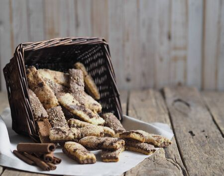 Homemade sandwich puff pastry chocolate cookies in a wicker natural basket of vines. Wooden ancient rustic table.